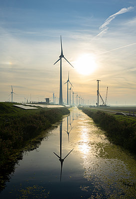 Wind turbines alongside canal at sunset - p1132m2215533 by Mischa Keijser