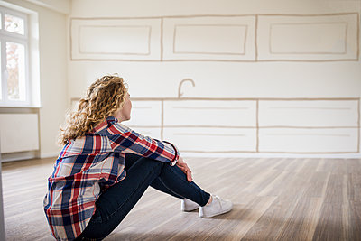 Young woman in new home sitting on floor thinking about interior design - p300m1460472 by Uwe Umstätter
