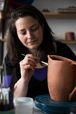 Potter painting unfinished vase in her workshop - p300m2118316 by Andrés Benitez
