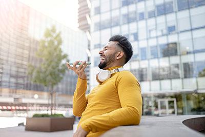 Cheerful man talking through smart phone in city - p300m2299159 von Jose Carlos Ichiro