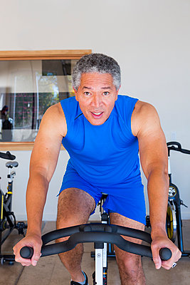 Mixed Race man riding stationary bicycle in gymnasium - p555m1301763 by Marc Romanelli