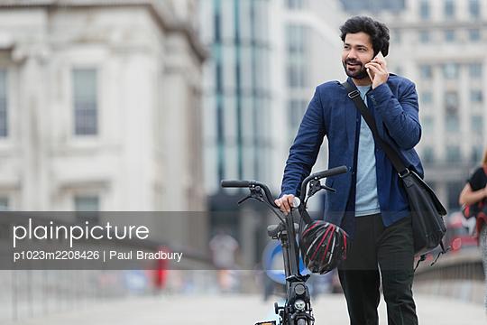 Businessman with bicycle talking on smart phone on city bridge - p1023m2208426 by Paul Bradbury
