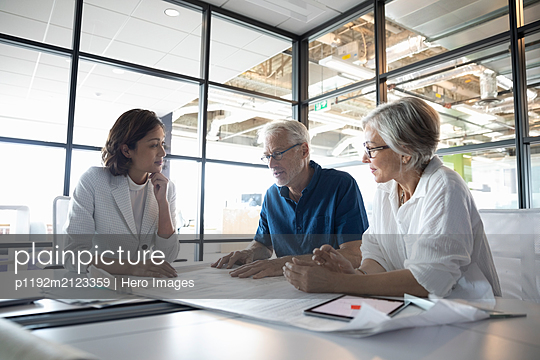 Clients discussing plans with design professional in studio - p1192m2123359 by Hero Images