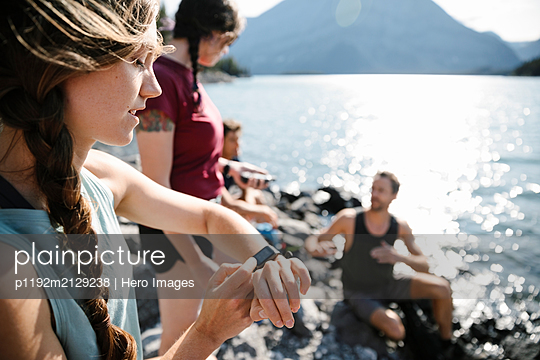 Female runner with smart watch at sunny lakeside - p1192m2129238 by Hero Images