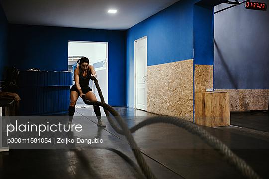 Woman exercising with ropes in gym - p300m1581054 von Zeljko Dangubic