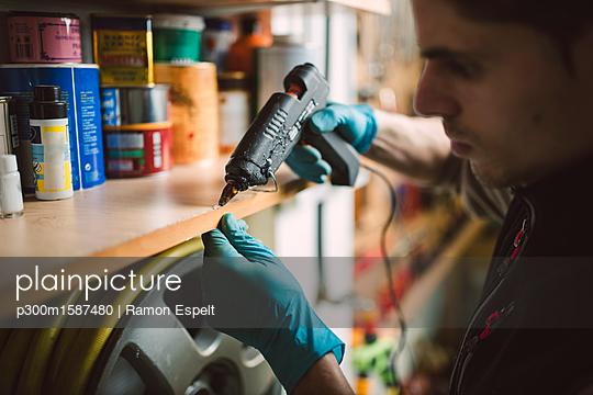 Man using a hot glue gun on shelf in workshop - p300m1587480 von Ramon Espelt