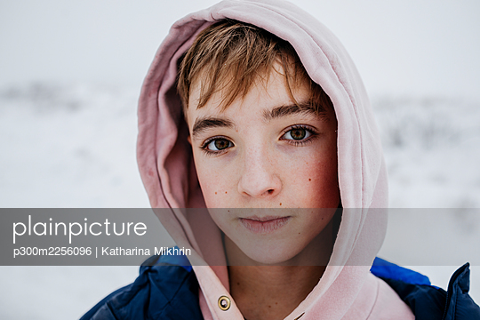 Teenage boy with brown eyes in warm clothing on snow - p300m2256096 by Katharina Mikhrin