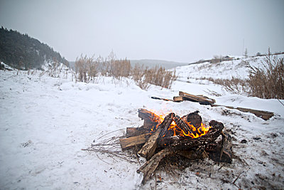 Bonfire on snow covered field against sky - p1166m1099722f by Cavan Images