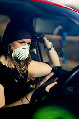 Woman in car wearing respirator mask using cell phone - p300m2181037 by Oscar Carrascosa Martinez