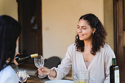 Woman pouring champagne in friend's wineglass while sitting by table at back yard - p300m2221086 by Francesco Morandini