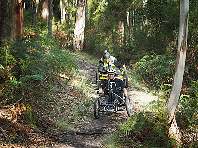 Men riding modified bicycles on forest path - p555m1304833 by PhotoAbility