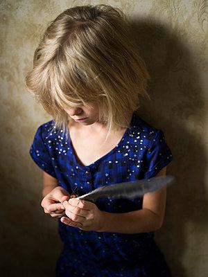 Blondes Mädchen hält eine Feder - p945m1475254 von aurelia frey