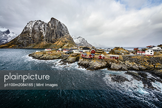 Snowy mountains overlooking rocky coastline, Reine, Lofoten Islands, Norway,Hamnoy, Lofoten Islands, Norway - p1100m2084165 by Mint Images
