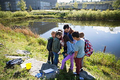 Science teacher and students at pond field trip - p1192m1078413f by Hero Images