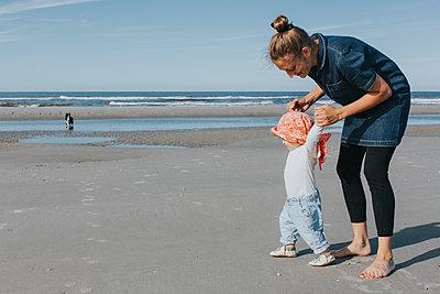 Netherlands, Schiermonnikoog, mother walking with little daughter on the beach - p300m1228487 by Daniel Weisser