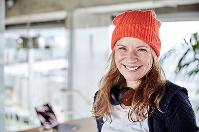 Smiling woman with knit hat at home - p300m2265219 by Jo Kirchherr