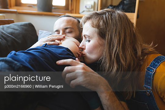 Affectionate family on the sofa with sleeping little son - p300m2166960 by William Perugini