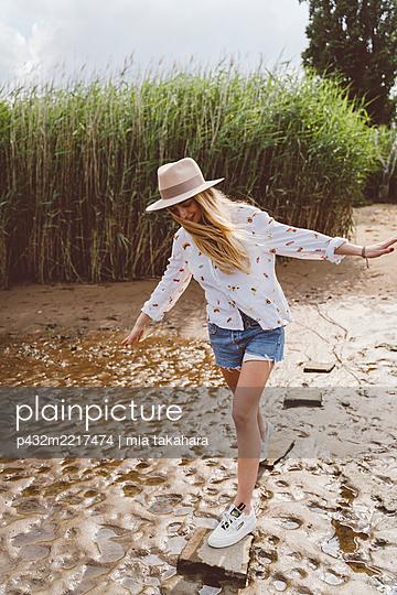 Attraktive junge Frau balanciert auf Steinen - p432m2217474 von mia takahara