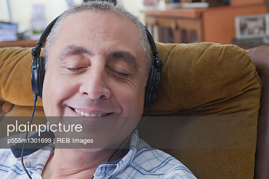 Smiling Hispanic man listening to headphones - p555m1301699 by REB Images