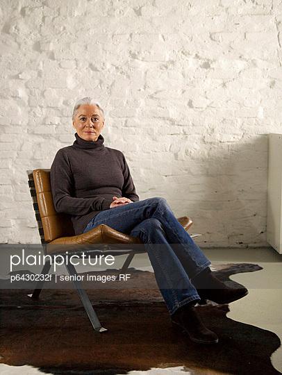 Aeltere Frau entspannt auf einem Sessel  - p6430232f von senior images RF