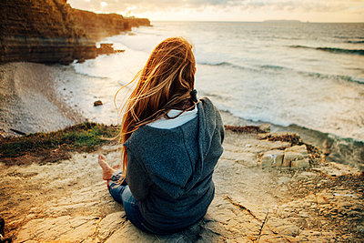 Rear view of woman sitting on cliff and looking at view during sunset - p1166m1186552 by Cavan Images