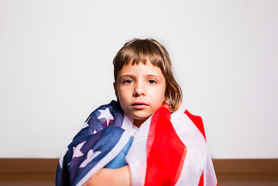 Beautiful portrait of a 6-year-old blonde girl wrapped in the American flag - p1166m2193942 by Cavan Images