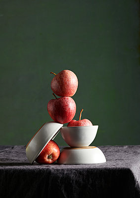 Apples and stacked dishes on a table - p1629m2211344 by martinameier
