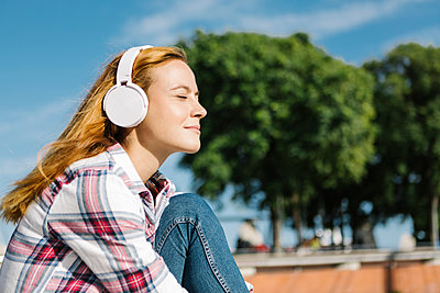 Woman with eyes closed listening music through headphone on sunny day - p300m2227368 by Xavier Lorenzo
