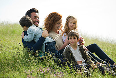 Family relaxing together outdoors - p6244127f by Eric Audras
