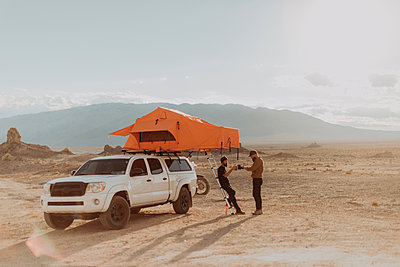 Motorcyclist friends taking break beside off road vehicle, Trona Pinnacles, California, US - p924m2068351 by Peter Amend