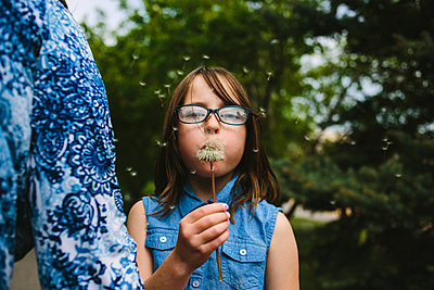 Portrait of girl blowing dandelion while standing in lawn - p1166m1231509 by Cavan Images