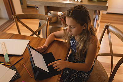 Girl using digital tablet at home - p1315m1579138 by Wavebreak
