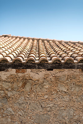 Tiled roof over a rustic stone wall under blue sky. - p1433m1584189 by Wolf Kettler