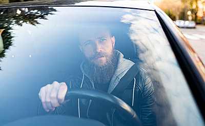 Bearded man driving car seen through windshield - p300m2242762 by Jose Carlos Ichiro