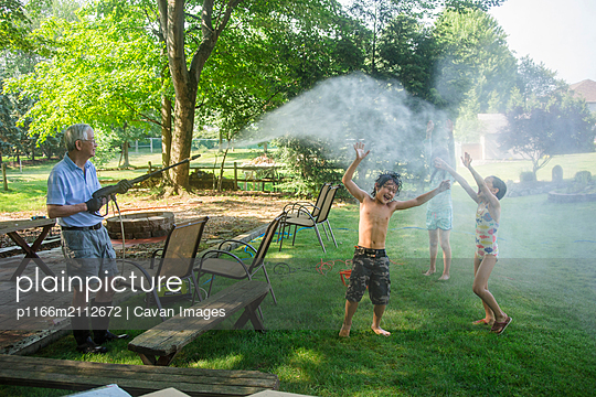 Grandfather spraying water on playful grandchildren at yard - p1166m2112672 by Cavan Images