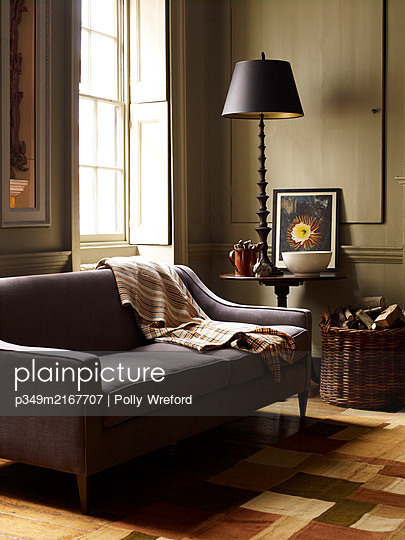 Lamp on side table with sofa and log basket - p349m2167707 by Polly Wreford