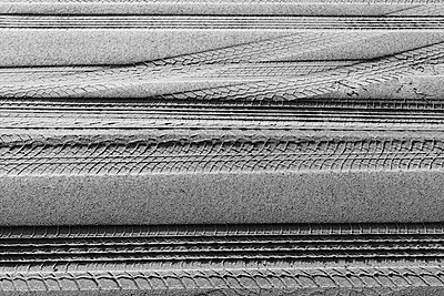Tire tracks on the soft surface of sand on a beach.  - p1100m2085127 by Mint Images