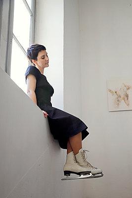Woman in black dress and ice skates on the windowsill - p1105m2244914 by Virginie Plauchut