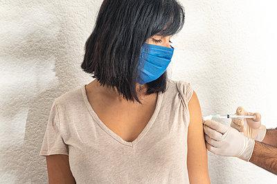 Coronavirus vaccine, woman get vaccine during coronavirus pandemic. - p1166m2236433 by Cavan Images