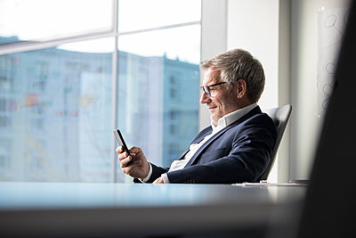 Businessman using cell phone in office - p300m1228638 by Rainer Berg