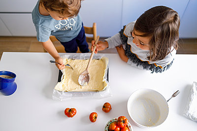 Brother and sister preparing food in kitchen - p300m2251842 by Ignacio Ferrándiz Roig