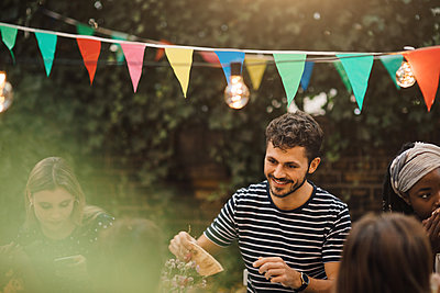 Smiling young man enjoying dinner party with friends in backyard - p426m2046164 by Maskot
