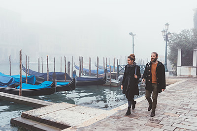 Couple strolling along misty canal waterfront, Venice, Italy - p429m1407780 by Eugenio Marongiu