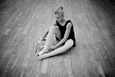 Caucasian ballerina tying pointe shoes - p555m1306056 by Vladimir Serov