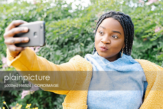 Portrait of young woman taking selfie with mobile phone - p300m2166524 by COROIMAGE