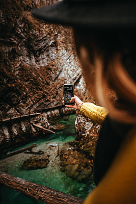 Woman taking a photo with her smartphone in the Vintgar Gorge in Slovenia - p1455m2081769 by Ingmar Wein