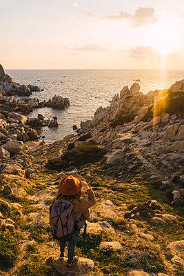 Italy, Sardinia, woman on a hiking trip standing on rock at the coast - p300m1581250 von Kike Arnaiz