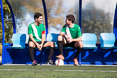 Two happy football players sitting on bench at football field talking - p300m2083019 by Andrés Benitez