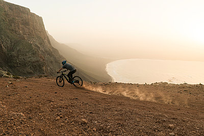 Spain, Lanzarote, mountainbiker on a trip at the coast at sunset - p300m2102609 by Hernandez and Sorokina