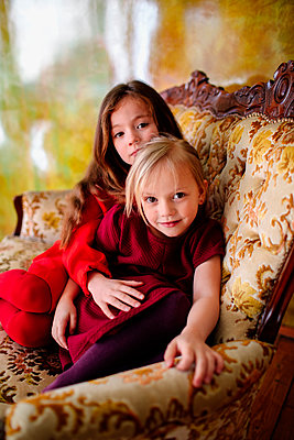 Portrait of two little sisters sitting together on lounge chair - p300m2121826 by Oxana Guryanova